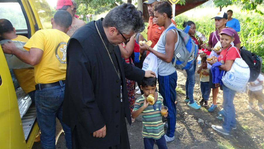 Working together, Greek Orthodox and Roman Catholic priests and Volunteer Ministers deliver food to refugees on the Colombian border.