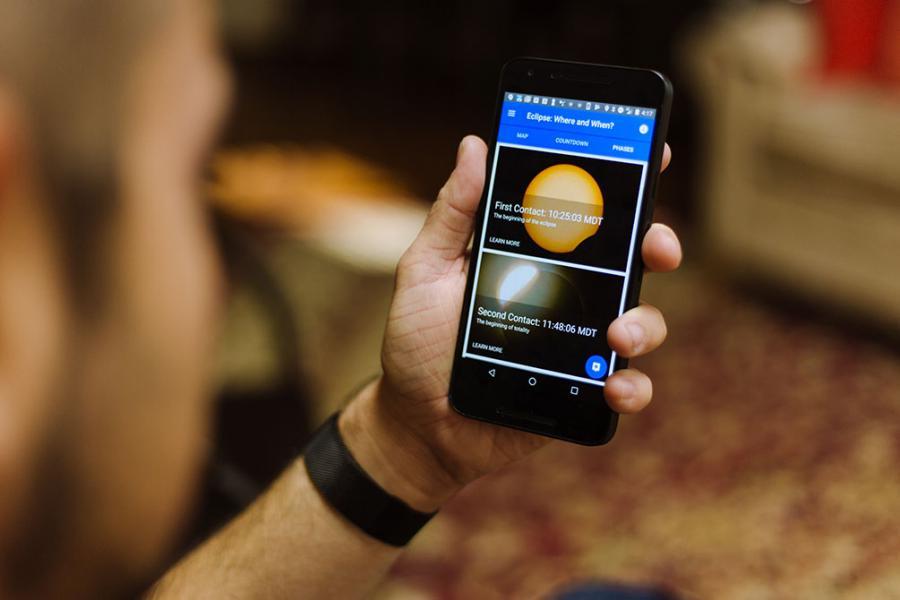 El hombre usando la aplicación Megamovie en su teléfono celular