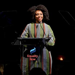 Chimamanda Ngozi Adichie smiling on stage behind a podium with the Equality Now logo on the front.