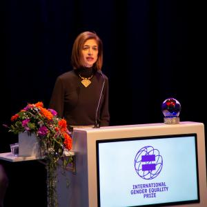 Equality Now's Yasmeen Hassan standing behind a podium on stage at Finnish Government's Gender Equality Prize  Ceremony 2019 speaking into a microphone to accept the