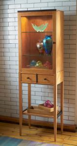 Standing tall on graceful legs, this meticulously constructed lighted cabinet is crafted in solid Pennsylvania cherry with dark wenge accents.