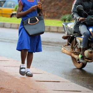 Anonymous photograph of a school girl around ten years old, wearing a sleeveless blue school uniform dress and carrying a black bag, walking along pavement past motorbike