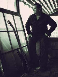 B&W Image of Michael Allison and guitar by window.