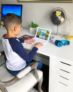 Young boy on a kids laptop where he can do his homework, write papers, conduct research, and have a more personalized learning experience.