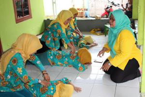Volunteers of a local posyandu in a suburb of Jakarta practice administering assists.