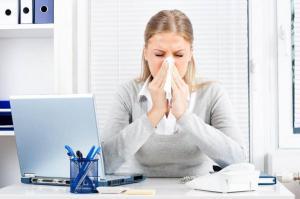 Woman sneezing in office