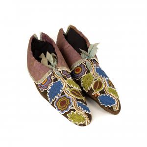 Pair of Cherokee moccasins, late 18th Century, black dyed buckskin with French silk brocade, ribbons and Italian cut beads in stylized floral patterns (est. $15,000-$25,000).