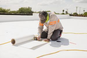 "alt=""Employee of McAllen Valley Roofing Co. measuring to cut a peice of roofing"""