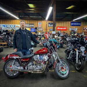 John Jessup, owner of Dream Rides stands next to a red motorcycle