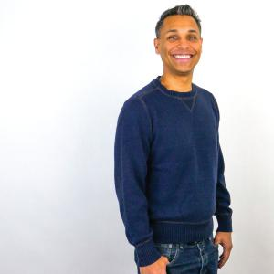 Joe Vega, in blue sweater and jeans standing in front of white background.