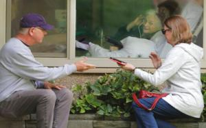 Man and woman visit with elderly relative through window.