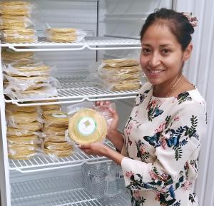 "Karla Plancarte, owner of ""Tortillería Taiyari,"" shows a sample of her specialty tortillas"