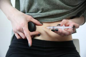 Woman using Buzzy while self-injecting medicine into her stomach