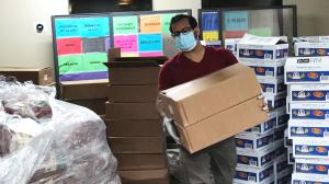A man wearing glasses with mask and gloves on carries a full cardboard box away from packing area