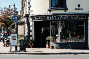 Woman shopping on sidewalk outside the storefront of a floral shop named, The Florist On The Corner.
