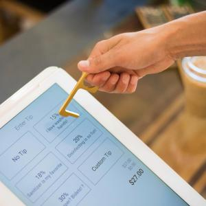 A Kontact key presses a checkout tablet with payment information.
