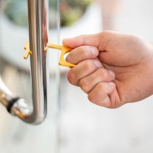 Hand holding a Kontact key opens door