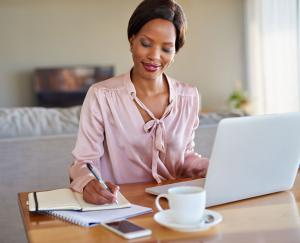 A woman wearing a light pink blouse writes in a notebook at her desk while working from home