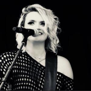 Diamonds & Whiskey lead singer Jennifer Webb sings on-stage.