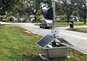NovoaGlobal's Portable Automated Enforcement System with solar panels on the side of the road as a car drives by.