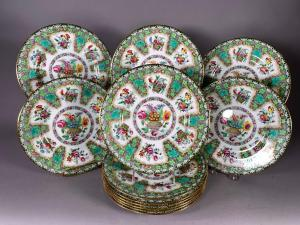 Set of twelve Spode Copeland dinner plates, decorated with floral baskets filled with colorful glazes against a green and white border (est. $400-$600). Each plate is 10 ¼ inches in diameter.