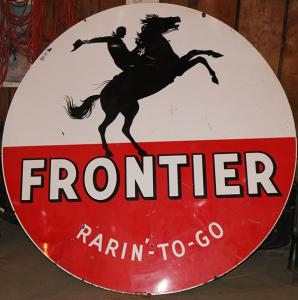 "Late 1950s Frontier Gasoline ""Rarin'-to-Go"" single-sided porcelain gas station sign, six feet in diameter, in excellent condition, with a graphic of a cowboy on a bucking bronco ($5,375)."