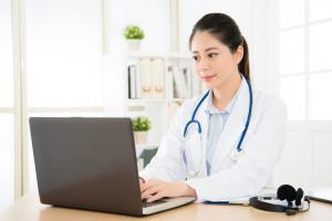 A female doctor wearing a white lab coat, with a stethoscope around her neck, sitting at a desk and typing on a laptop