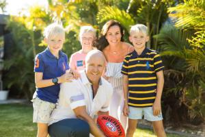 Tucker Family, Sam, Cindy and their boys Zac, Axel and Jordan holding an Australian Football