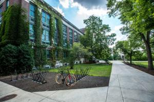 empty college campus with bicycle rack and ivy on the building
