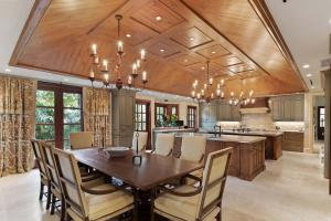 The gourmet kitchen features two islands, a stunning vaulted wood ceiling, and chandeliers.