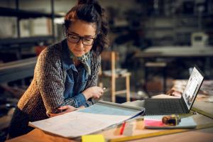 Woman working in home office, looking at complex product drawings while working remotely