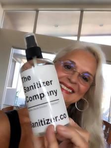 The Sanitizer Company's Anna Miller holding a bottle of Toprosan™ 75% ethyl alcohol liquid sanitizer.  It kills COVID 19