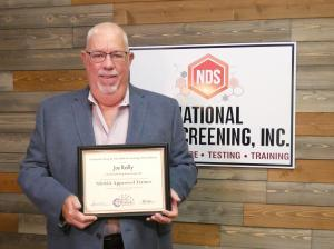 Joe Reilly holding Trainer Recognition Award from NDASA