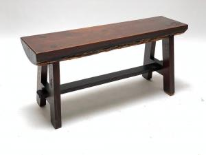 Early 20th century Roycroft Ali Baba bench featuring a plank seat retaining bark to the underside and presented on a trestle-style base joined by a mortise and tenon jointed stretcher ($17,220).