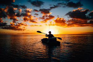 man on kayak during beautiful sunset