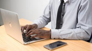 man sitting at desk working on laptop computer with cell phone nearby