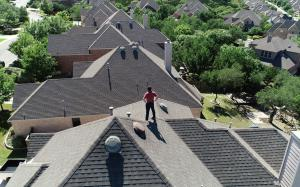 McAllen Valley Roofing Co. managing partner standing on top of a residential house.