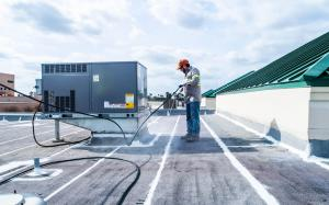 McAllen Valley Roofing Co. crew member spraying silicone on a commercial flat roof.