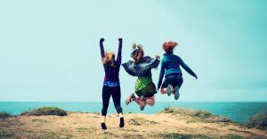 Empowered women jumping near a gorgeous blue ocean