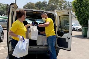 Volunteers from the Center of Scientology Israel distribute food and other supplies to those in need to help them get through the pandemic.