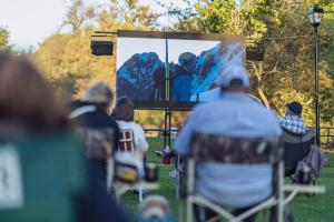 An audience at the Chagrin Documentary Film Festival watches films in the park.