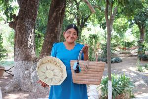 A woman holds up two locally made products.