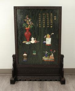 Large and impressive jade table screen (or panel) with numerous scholars' items pictured in relief, 29 ½ inches by 42 ½ inches, with carved stone appliqued items (est. $3,000-$5,000).
