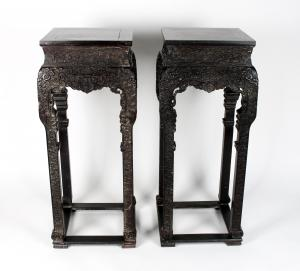 Pair of 40-inch-tall antique carved zitan vase stands, both elaborately carved all over, the tops of the legs have pierced designs of dragons, the legs carved in cloud forms (est. $1,500-$2,500).