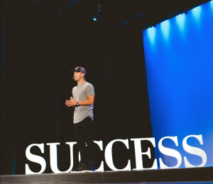 Peter Voogd on stage talking about business success.