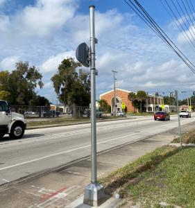 Photo of Red light camera enforcement on side of road monitoring traffic as cars drive by