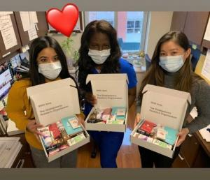 3 ladies each with a box filled with wellness products.