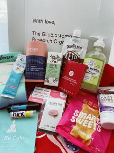 White box opened with several products inside such as hand sanitizer, peanut butter pouch, pins, stickers, socks, and beauty products.