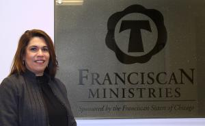 Photo of Monica Simzyk, the Chief People Officer for Franciscan Ministries, standing in Ministry Office in front of