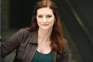 Woman, red hair, brown jacket leaning over with right arm bent